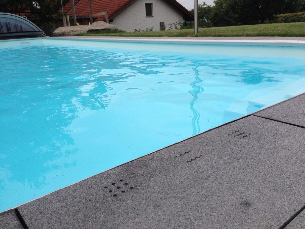 ovládací tlačítka gravírovaná v betonu pro inteligentní bazén