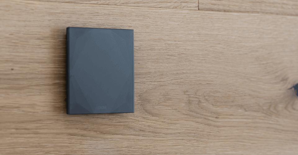 Černé skleněné tlačítko Loxone na dřevěném podkladu