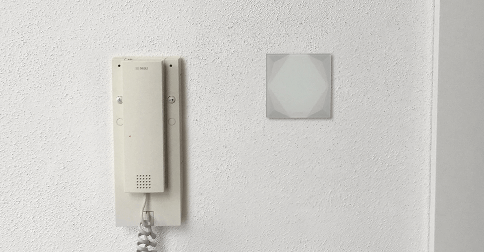 Chytré tlačítko Loxone Touch Pure vedle starého domovního telefonu