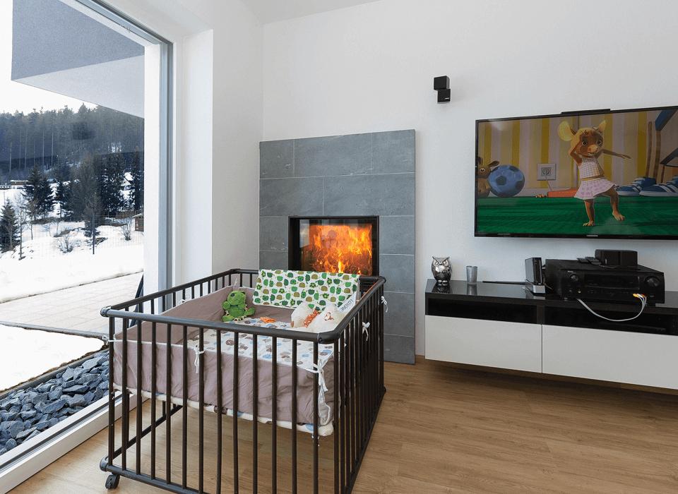 Dětská postýlka v místnosti s krbem a velkým oknem