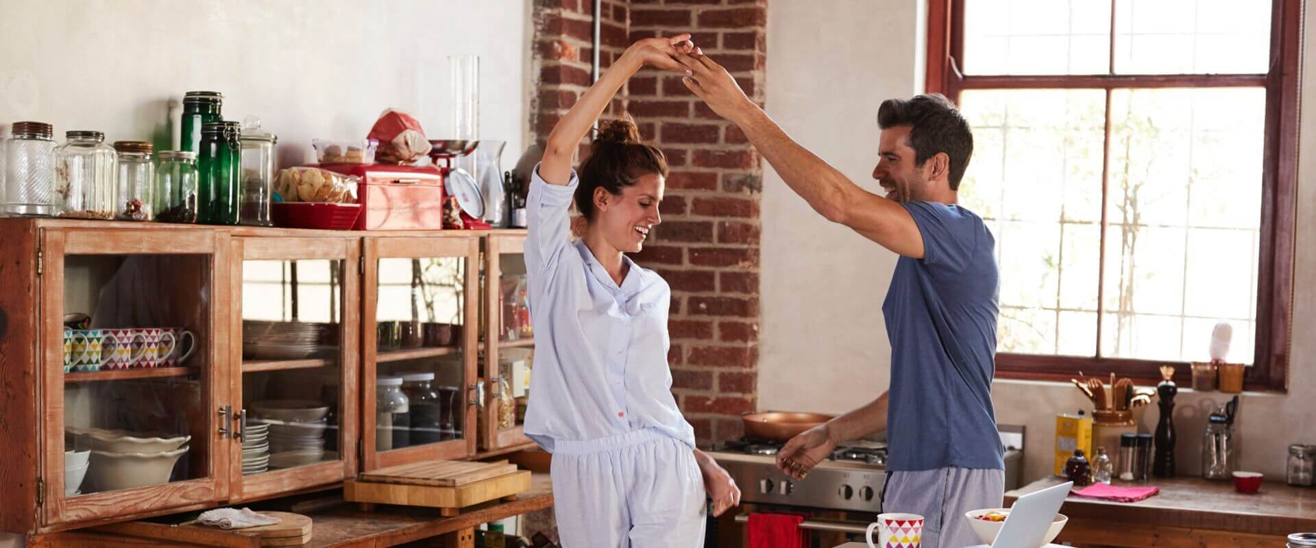 muž a žena tancují doma za doprovodu hudby