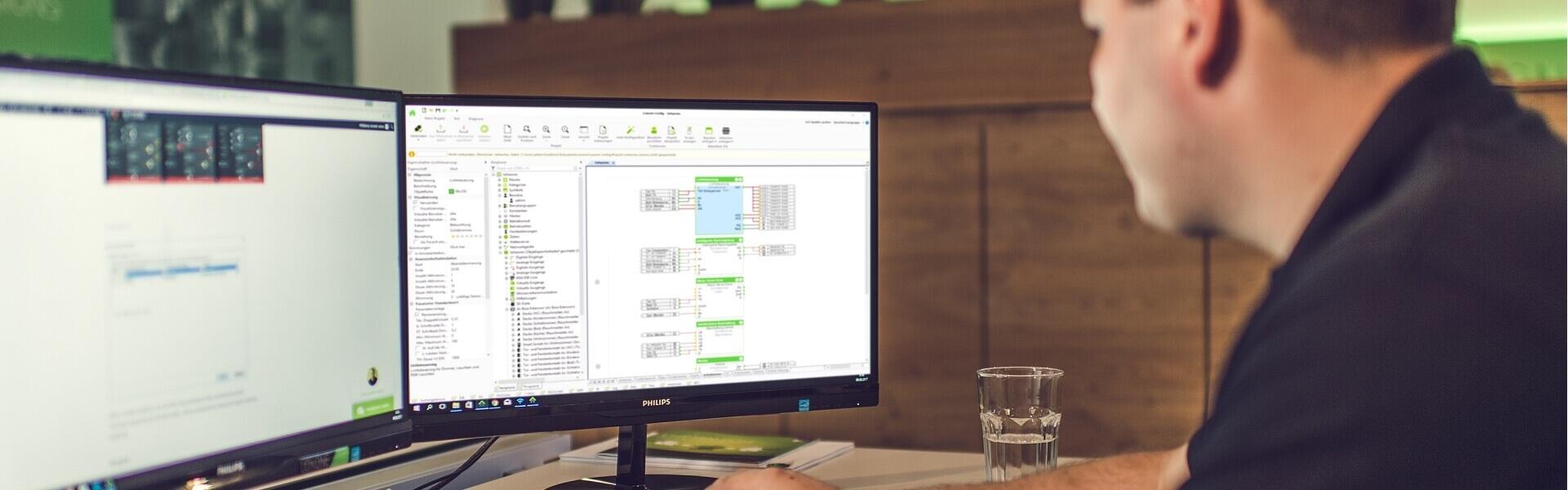 muž programuje na dvou monitorech