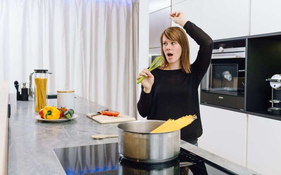 žena poslouchá hudbu v kuchyni