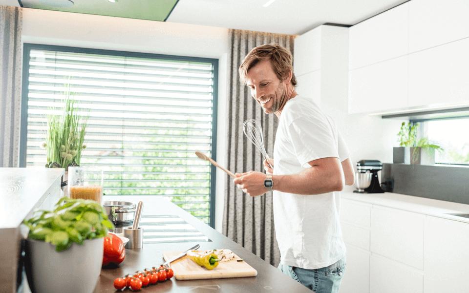 mladý muž poslouchá hudbu při vaření v kuchyni