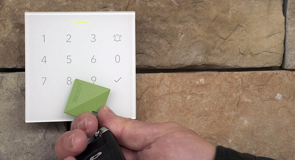NFC přívěsek přiložený ke skleněné Loxone klávesnici NFC Code Touch