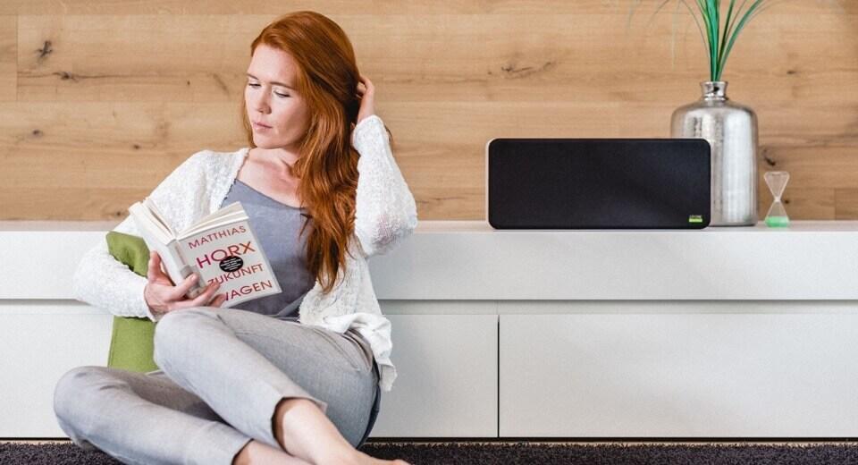 žena si čte knihu u reproduktoru