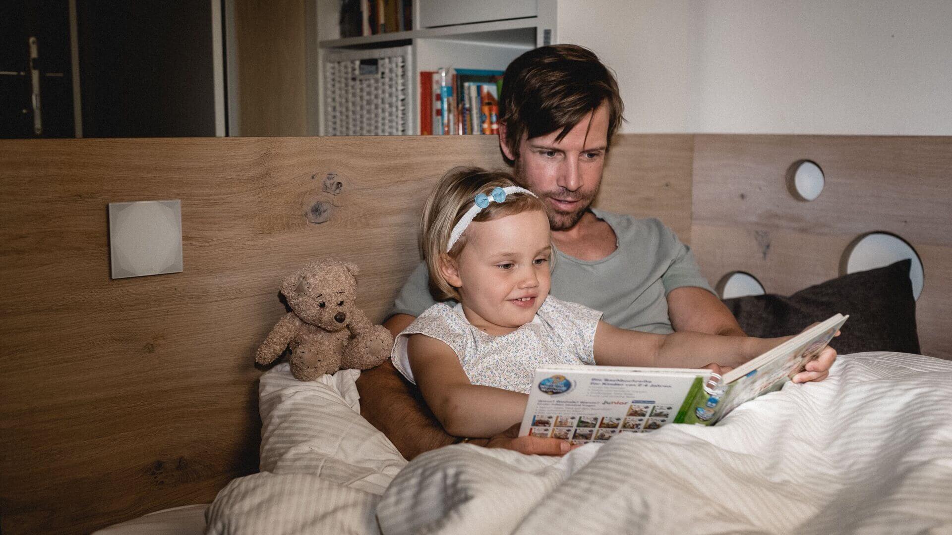 muž čte své dceři pohádky v posteli