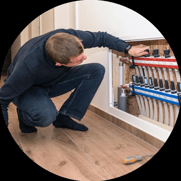 muž se snaží nastavit teplovodní podlahové vytápění domu