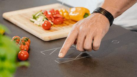 mužská ruka ovládá chytré tlačítko integrované v kuchyňské lince
