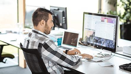 muž u stolu pracující na počítači Apple Macbook
