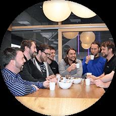 skupina zaměstnanců při hovou u kávy na baru