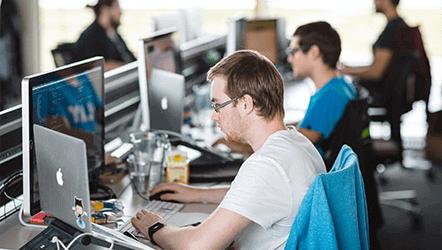 zaměstnanci u pracovních stolů s počítači