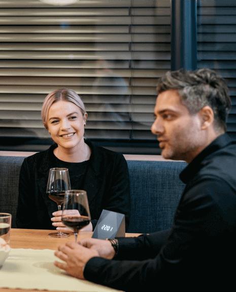 Přátelé se sklenkou vína s chytrým tlačítkem na stole