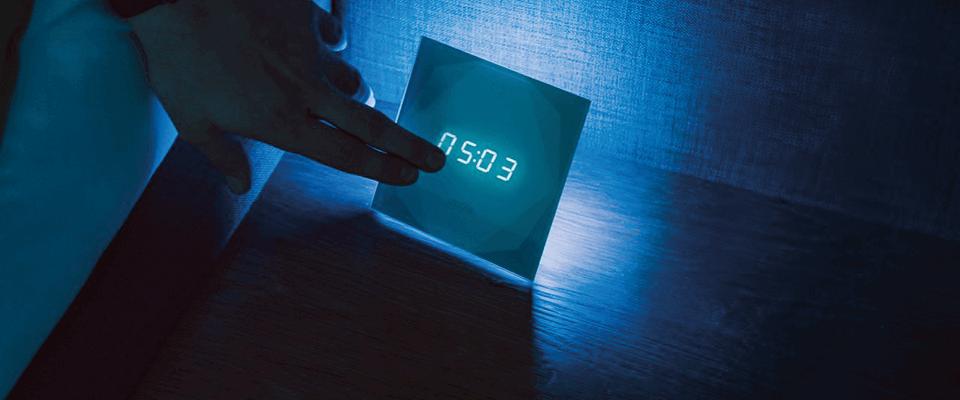 ruka se dotýká chytrého budíku touch nightlight s nočním osvětlením