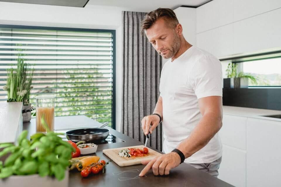 muž krájí zeleninu a ovládá při tom chytré tlačítko integrované v kuchyňské desce