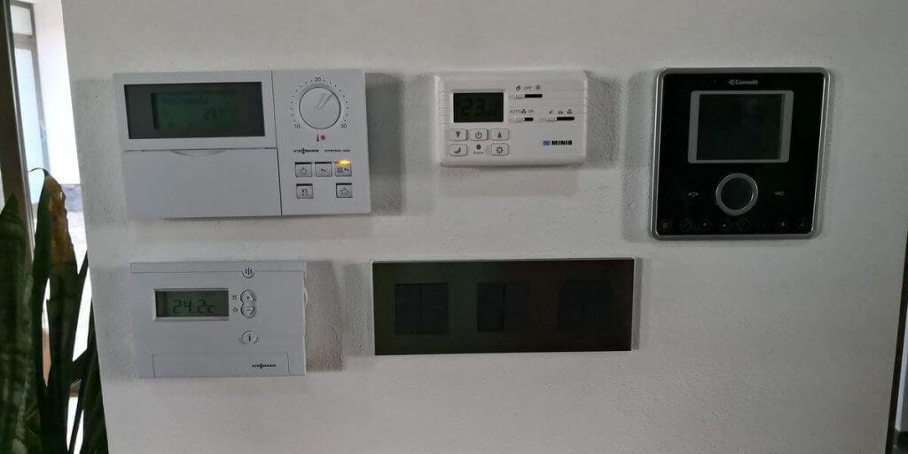 Zeď zaplněná mnoha tradičními ovládacími prvky pro technologie v domě.