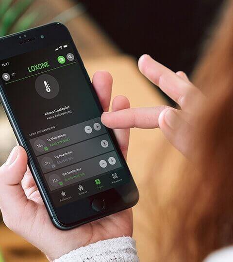 Žena ovládá domácnosti pomocí aplikace Loxone v telefonu
