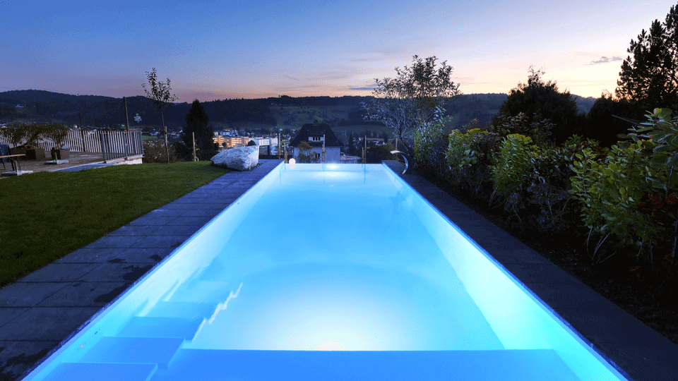 Atmosphärisch beleuchteter Pool im Garten