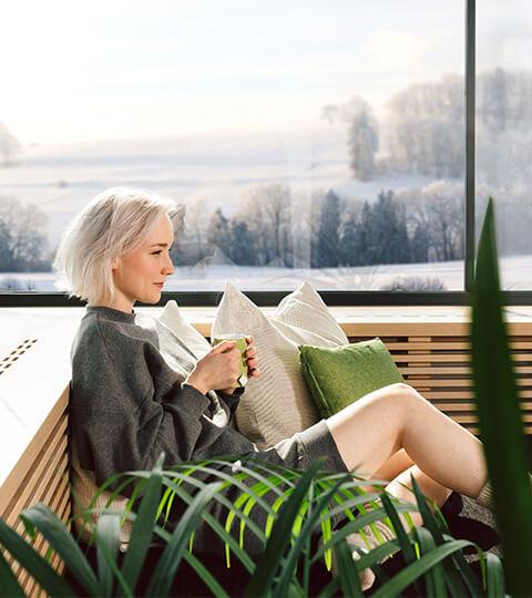 Žena na pohovce u okna