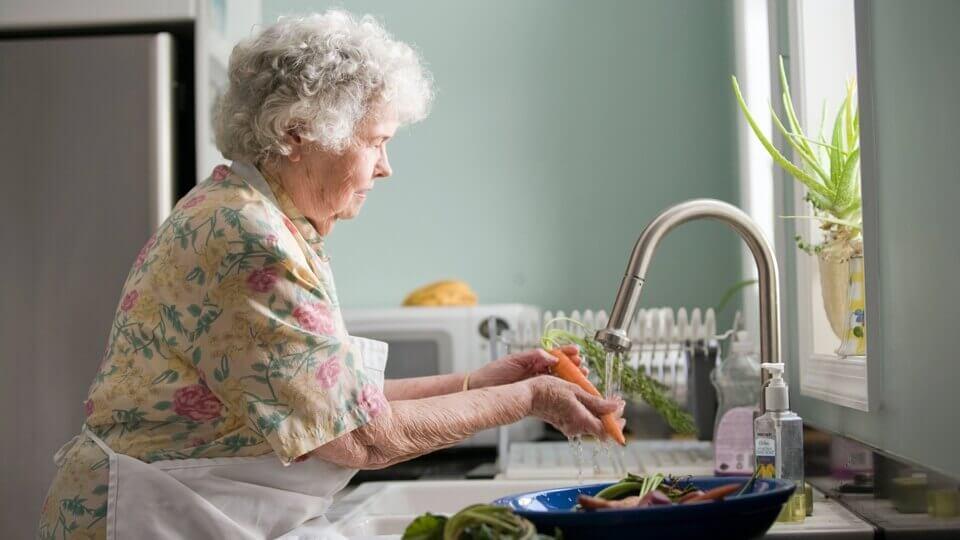 Důchodkyně umývající zeleninu.
