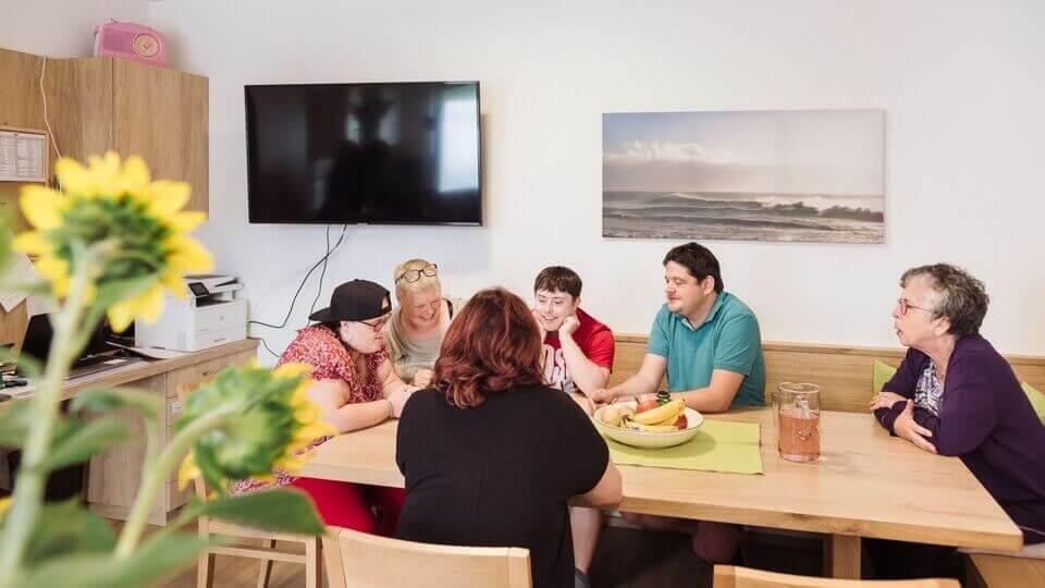 Osoby potřebující asistovanou pomoc spolu s ošetřovateli v jídelně