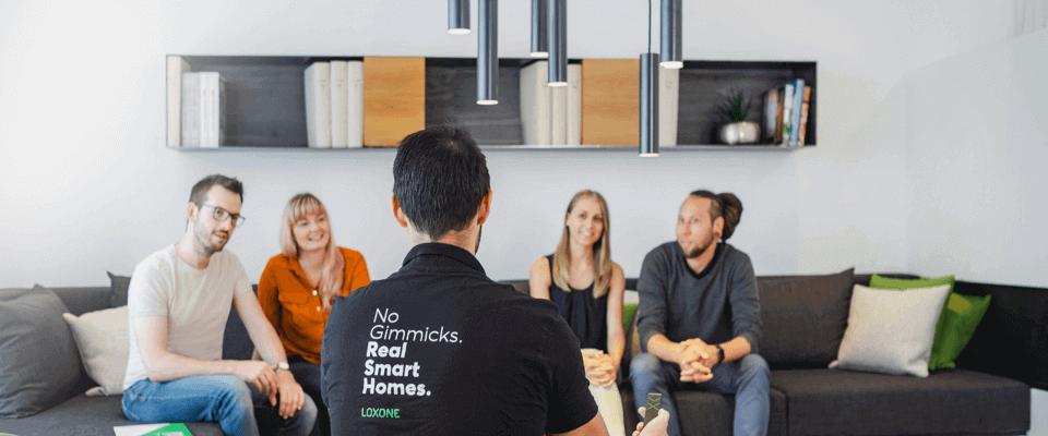 Ľudia sediaci v obývačke s Loxone konzultantom