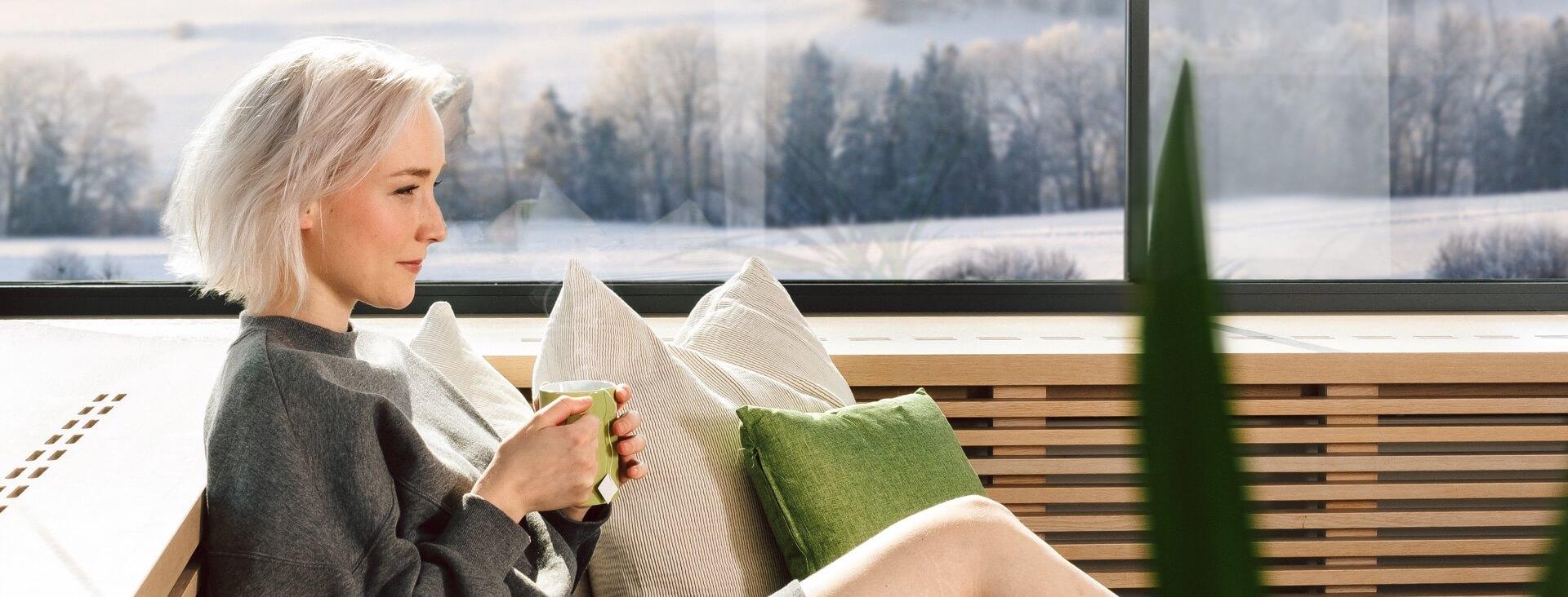 Frau mit Teetasse neben Heizung