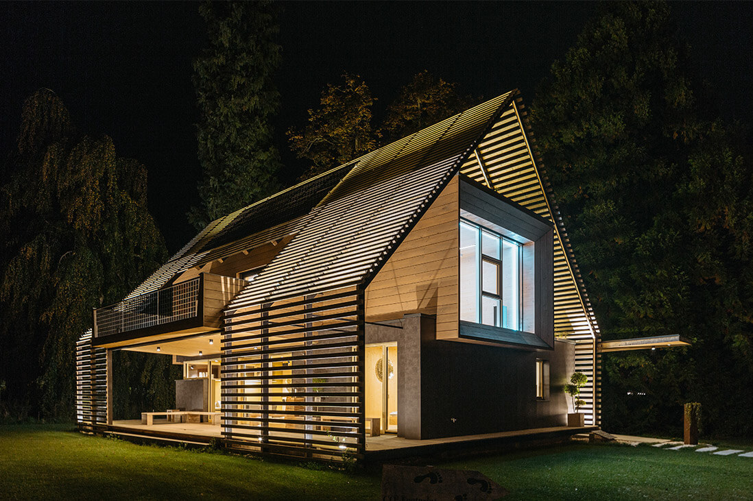 Beautiful energy efficient home glowing at night with wooden slat exterior.
