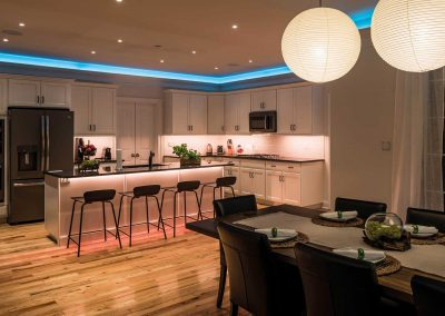 Dining room and kitchen of Loxone Showhome with colorful accent lighting.