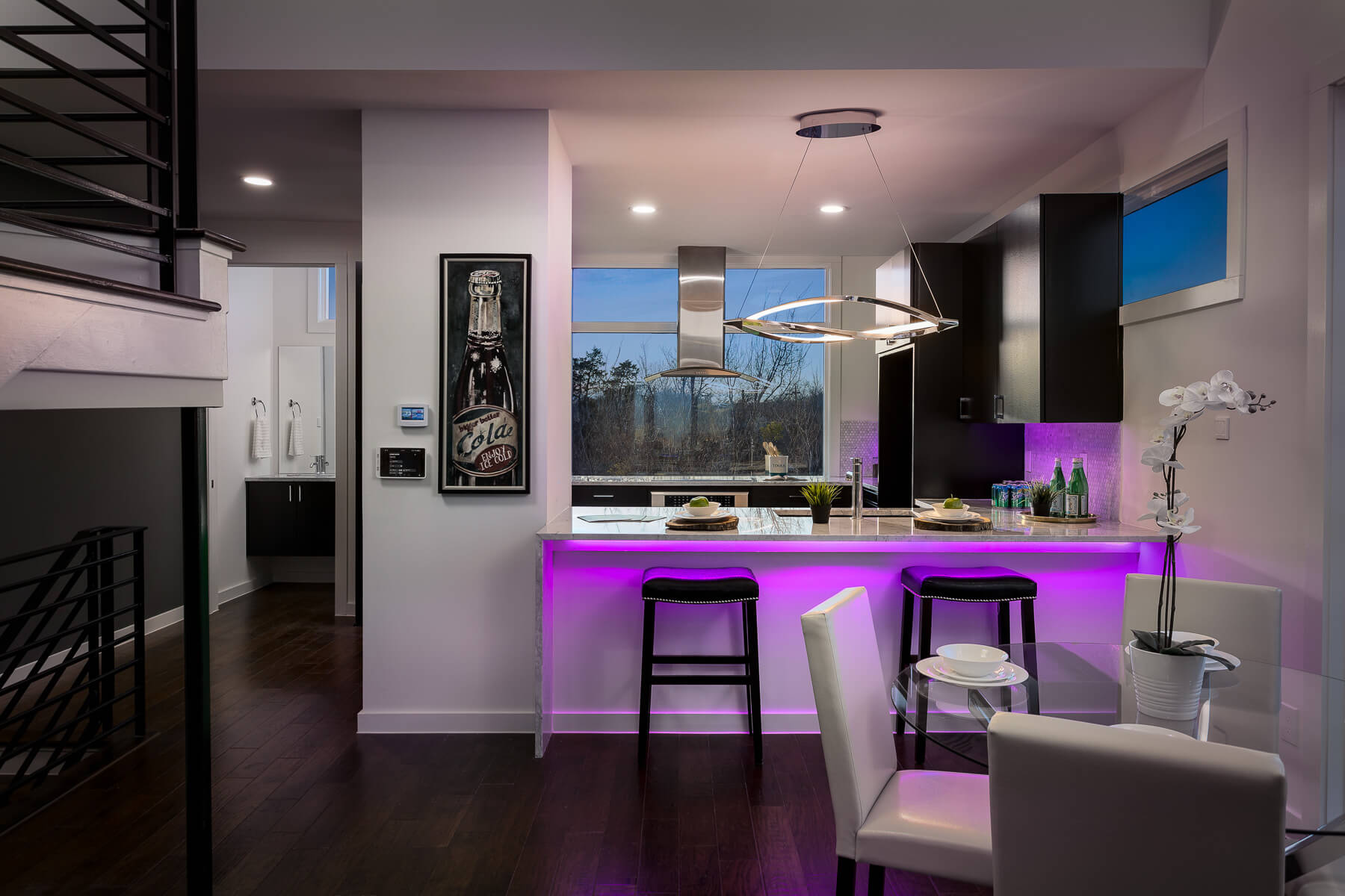 Modern kitchen with white interiors and purple accent lighting beneath counter top.
