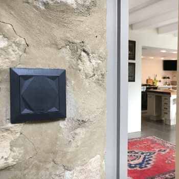 Loxone Touch hanging on marble wall.