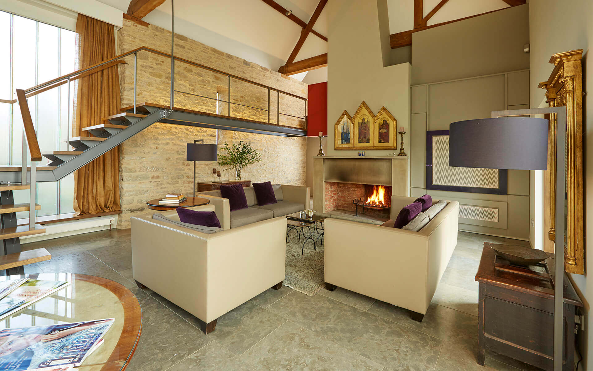 Open living room with fireplace and suspended walkway with stairs.