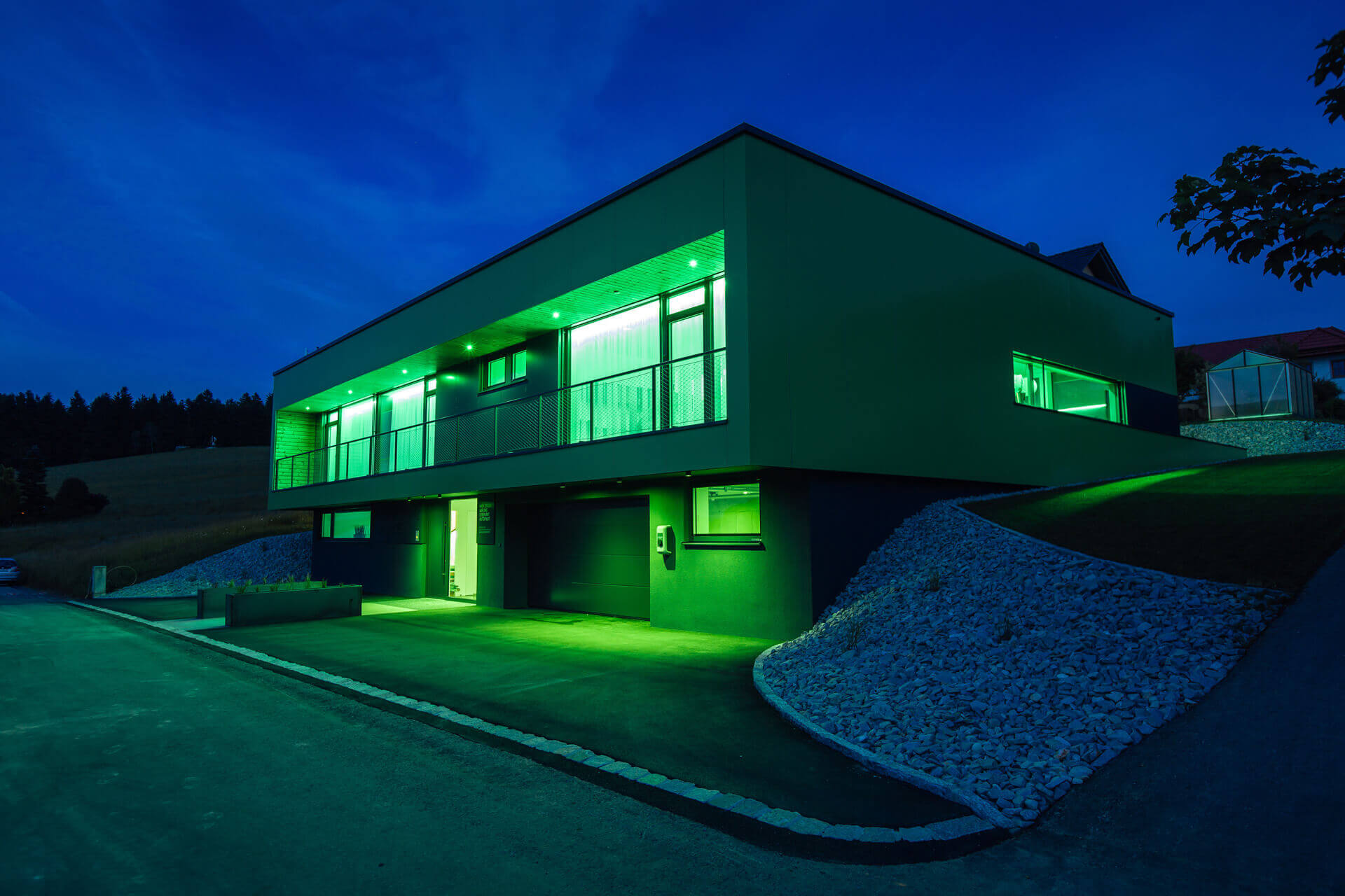 Modern, rectangular, bright green and black smart home on a sunny day.