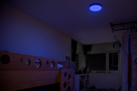 Ceiling light with dim blue light in bedroom at night.