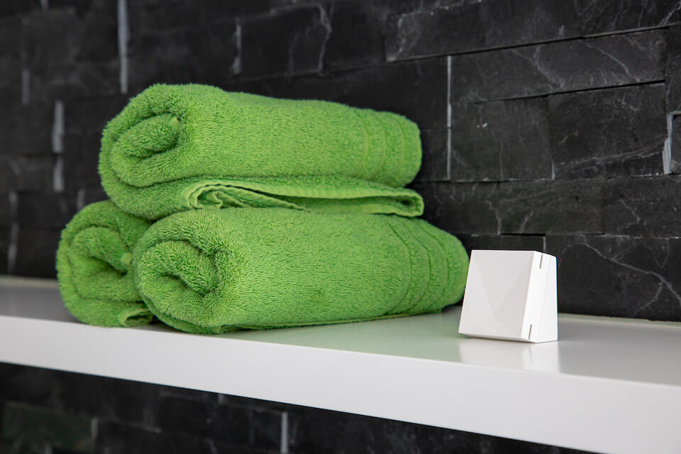 Loxone Room Comfort Sensor placed on shelf next to towels