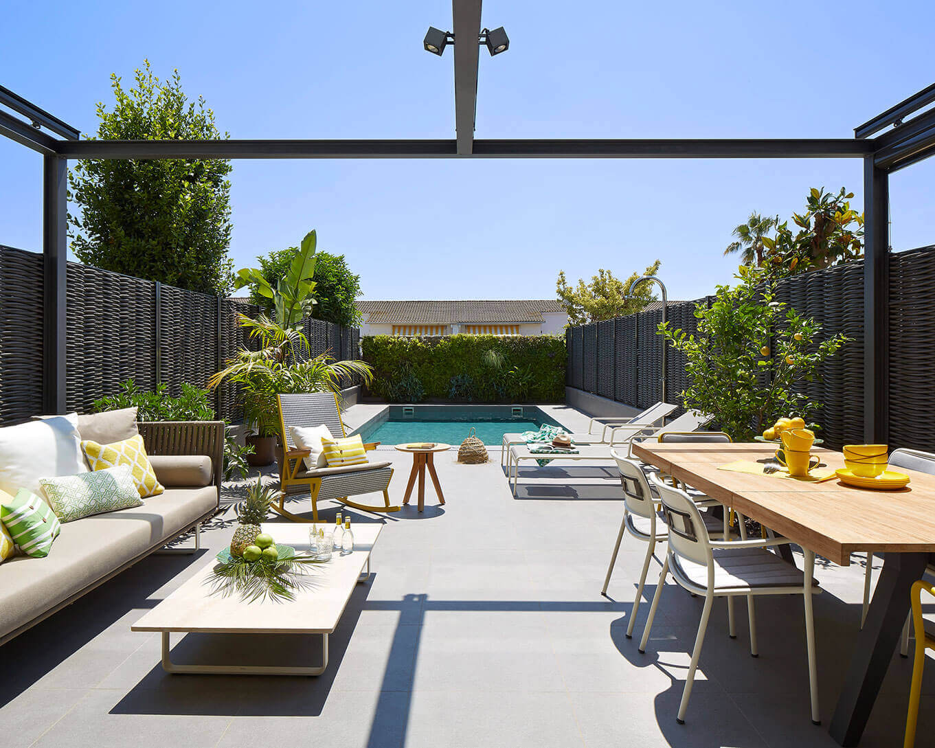 Outdoor lounge area with pool and plants.
