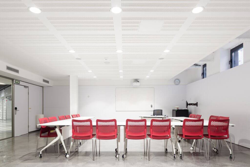 Brightly lit room with tables and bright red chairs.