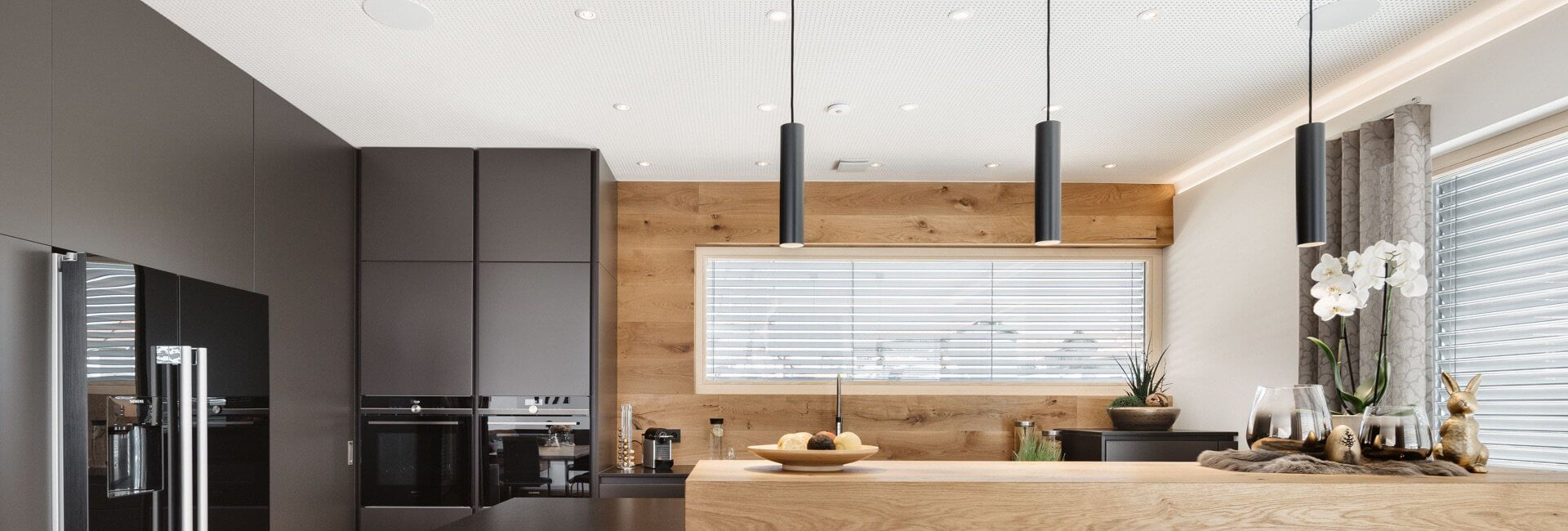Kitchen with black cabinets and natural wood accents with LED Pendulum Slim lighting