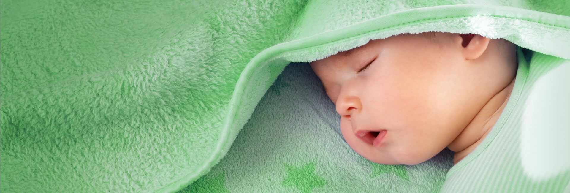 Baby sleeping peacefully wrapped in blanket.