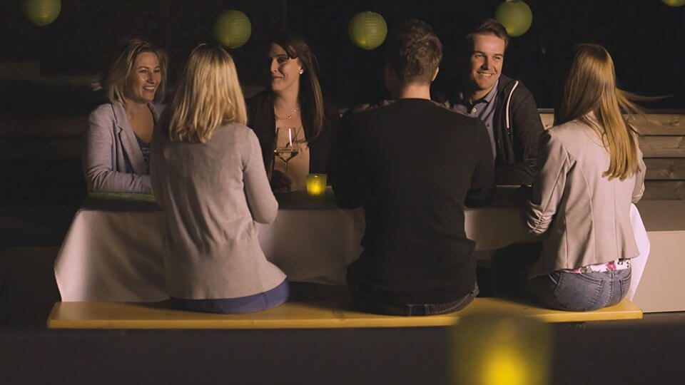 Group of friends sitting around an outdoor table at night.