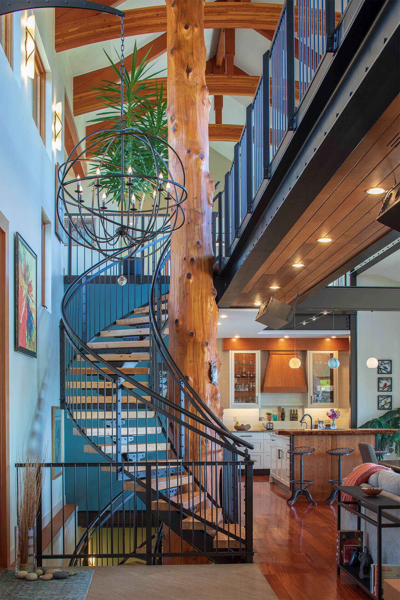Spiraling staircase around reclaimed tree with lighting fixtures