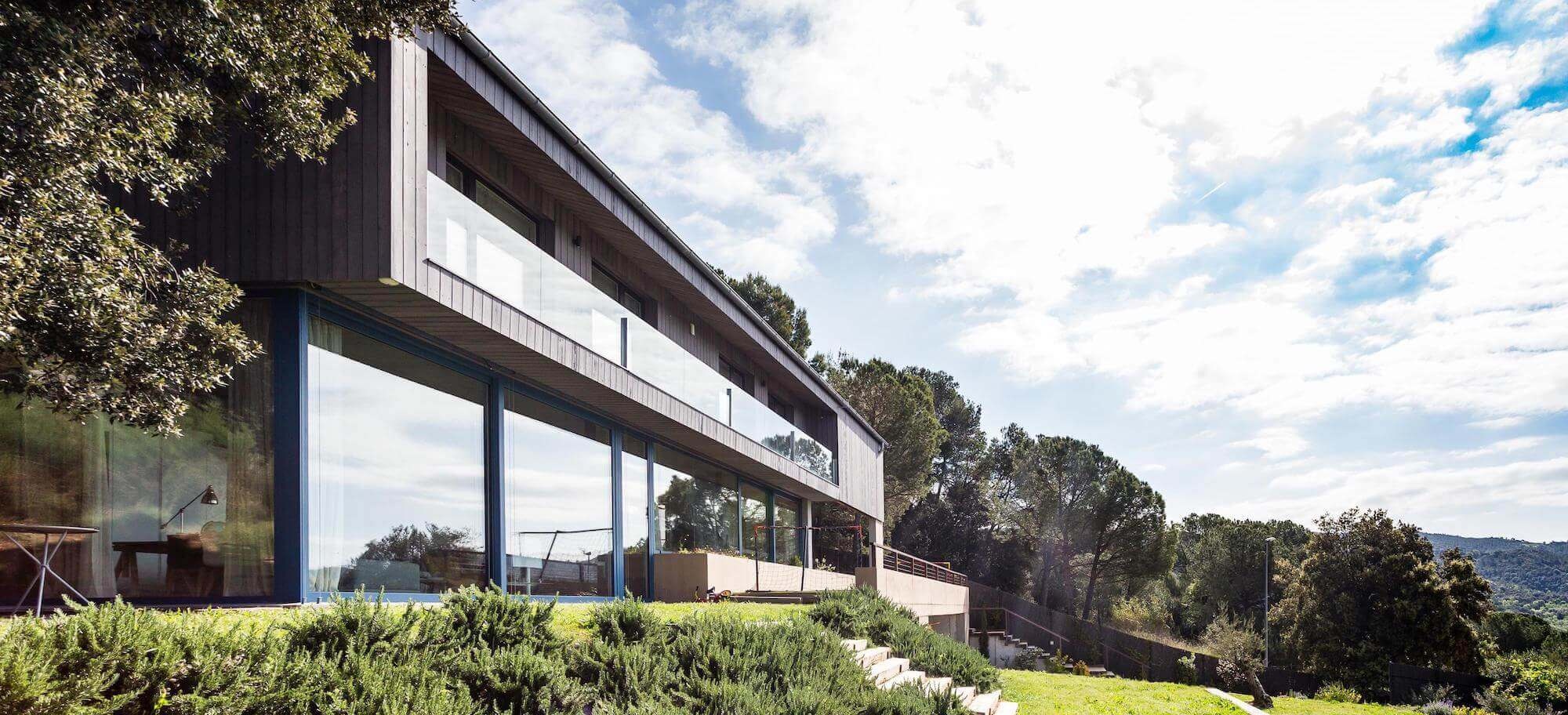 Exterior of Passive House Girona with bright sky.