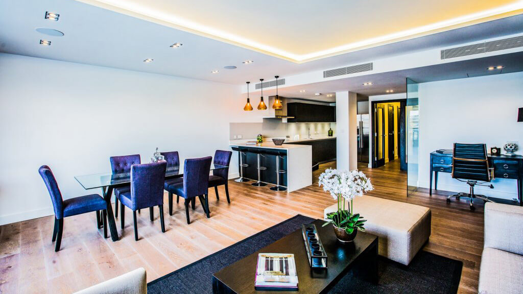 Brightly lit apartment with LED Strips along the ceiling.