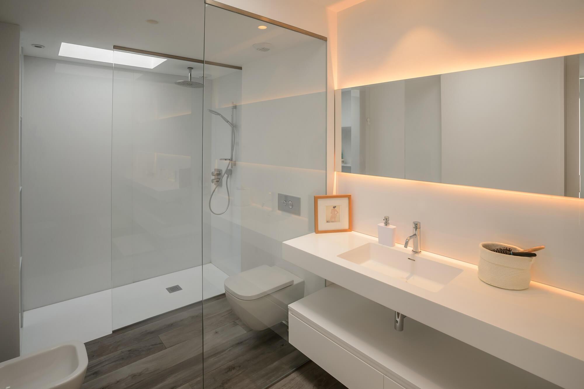 bílá koupelna v minimalistickém stylu s velkým zrcadlem podsvíceným LED páskem