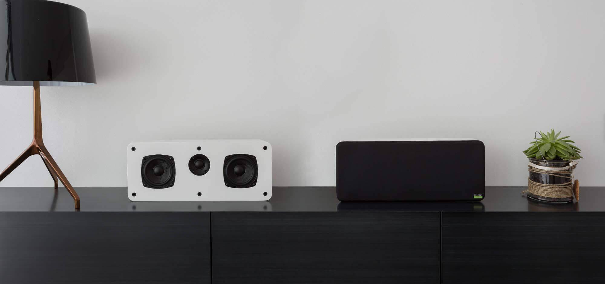 Czarna półka na której stoją dwa głośniki Wall Speaker