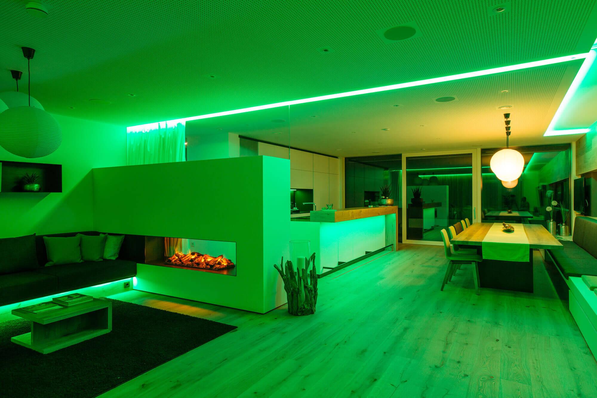 Duży pokój który jest oświetlony na zielono z białymi ścianami i ciemnymi meblami