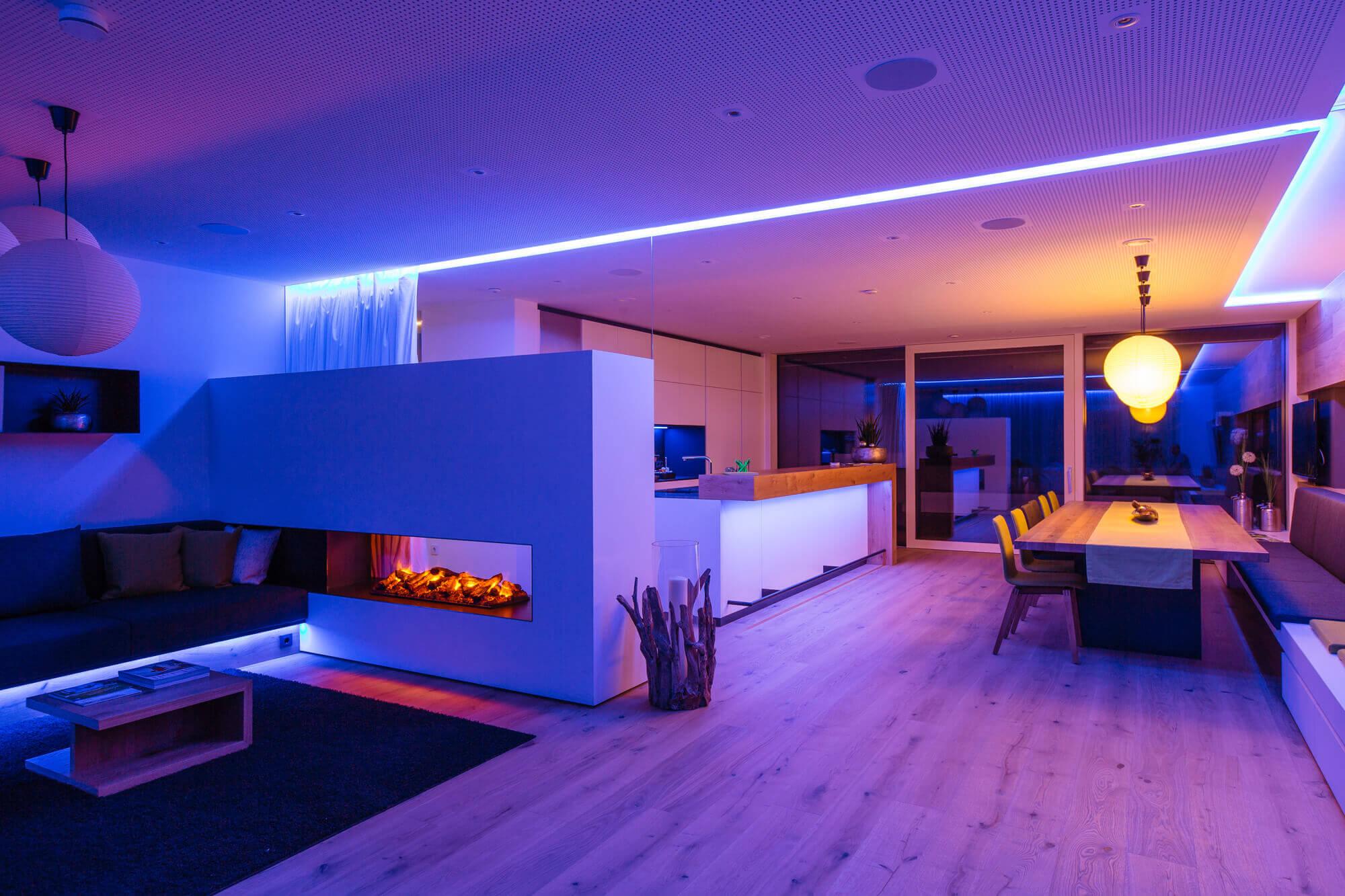 Duży pokój który jest oświetlony na niebiesko z białymi ścianami i ciemnymi meblami