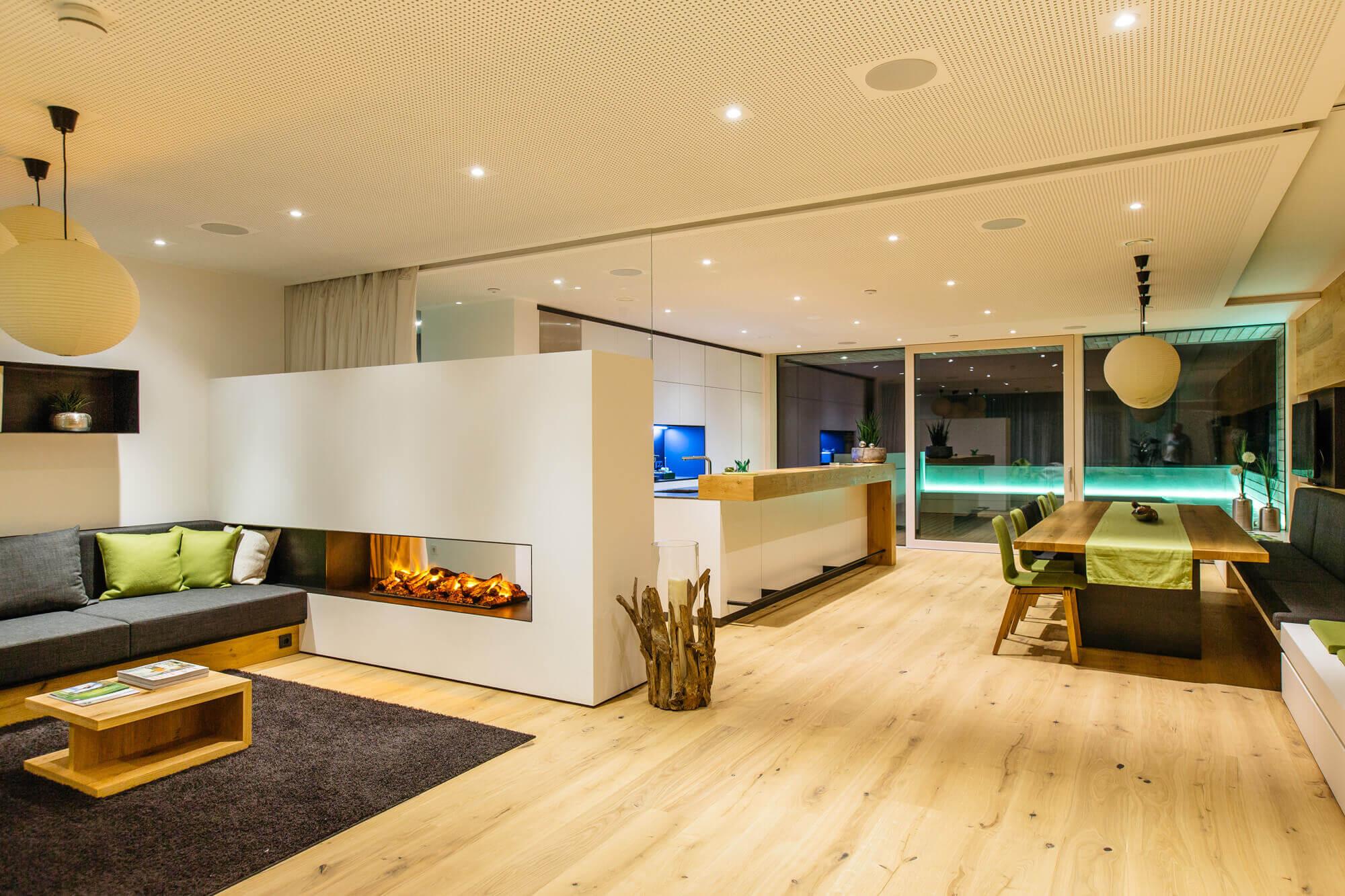 Duży pokój który jest dobrze oświetlony z białymi ścianami i ciemnymi meblami