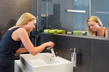 Kobieta myje się nad umywalką