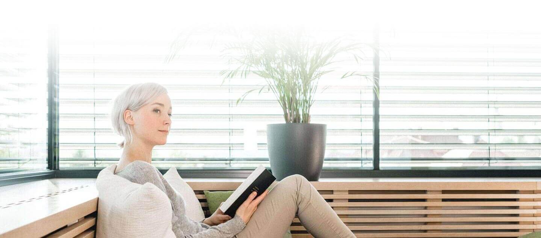 Kobieta siedząca na ławce i czytająca książkę.